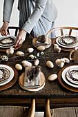 Frau deckt alten Holztisch mit rustikaler Naturdeko