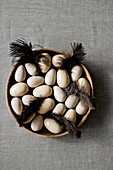 Wooden and ceramic eggs and brown feathers in wooden bowl