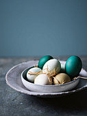 Various coloured eggs with straw in a ceramic bowl