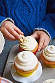 Kinderhand dekoriert Cupcakes mit Plätzchen