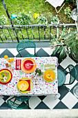 Farbenfroh gedeckter Terrassentisch mit Blumentischdecke