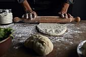 Pizzateig mit Nudelholz ausrollen