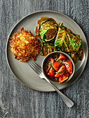 Savoy cabbage and game roulade with potato fritters and tomato salad