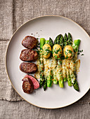 Gratinated green asparagus with young venison steaks and salted potatoes