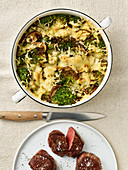 Potato and broccoli gratin with game medallions
