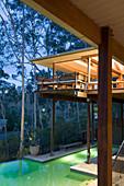 Modernes Architekten-Holzhaus auf Stelzen mit Pool bei Abendbeleuchtung