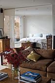 Wohnraum mit brauner Polstergarnitur und durch Vorhang abgetrenntem Schlafbereich im Hintergrund