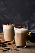 Chai latte in glasses with milk foam and anise stars