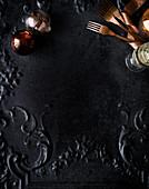 Weihnachtskugeln, Gabeln und Weinglas auf schwarzem gusseisernem Untergrund