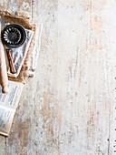 Buch, Teigroller, Messer und Backförmchen auf Holzuntergrund