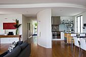 Offener Wohnraum mit Küchenbereich abgetrennt durch gebogene Wand