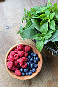 Berries in a wooden bowl next to a wire basket of herbs