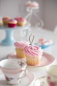 Cupcakes mit rosa Cremehaube auf romantisch gedecktem Tisch