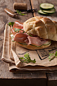 A bread roll with mortadella, cucumber and rocket