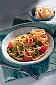 Spaghetti with fava beans, cherry tomatoes and roasted onions