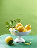 Zitronen mit Blatt in weisser Schale