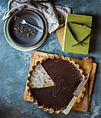 Chocolate tart with biscuit base and slice removed