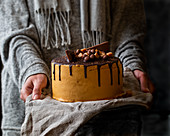 Chocolate and salted caramel cake with hands holding it