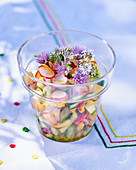 Vegetable salad with fruit and chive flowers