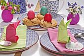 Napkins folded into bunnies and DIY papier-mâché vases on Easter table