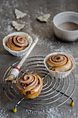 Cinnamon buns with icing on a wire rack