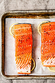 Fresh Salmon in a baking tray, ready for the oven, with slices of lemon