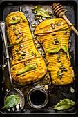 Hasselback-Butternusskürbis mit Lorbeer und Kürbiskernen auf Ofenblech