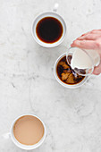 Three coffee cups with coffee and milk