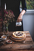Woman pouring melted dark chocolate on a stack of crepes