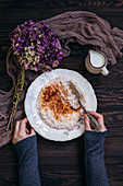 Frau isst Milchreis mit Zucker und Zimt