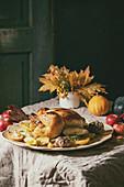 Brathuhn mit Knoblauch und Kartoffeln auf herbstlich gedecktem Tisch