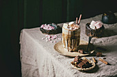 Hot chocolate or cocoa with marshmallow served in ceramic mug with saucer and thuja branch on grey table cloth