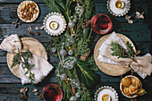 Christmas or New year table setting with empty ceramic plates, wine glasses, napkins, Christmas thuja wreath, luminous garland and burning candles on dark wooden plank table. Holiday mood flat lay