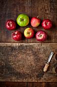 Rote und grüne Äpfel auf Holzuntergrund