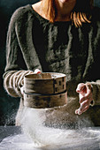 Process of making homemade bread dough: Woman hands sifts flour from vintage sieve