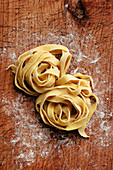 Nest of homemade pasta on wooden board