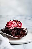 Schokoladen-Cupcake mit rosa Frosting, angebissen