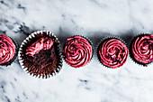 Schokoladen-Cupcakes mit rosa Frosting, einer angebissen