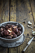 Chestnuts in a clay bowl on a wooden background