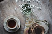 Chemex-Karaffe, Kaffeetasse und Glasvase auf Holztisch