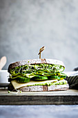 A healthy cheese and green salad sandwich on brown bread, with cucumber and cress