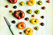Verschiedene Heirloom-Tomaten mit Messer auf grünem Holzuntergrund