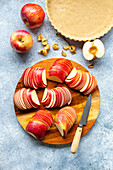 Preparation of an apple tart: Sliced apples on a wooden board