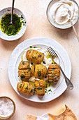 Roasted hasselback potatoes with parsely dressing on a plate