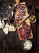 Entenschinken, Bresaola und Beef Jerky mit Pickles, Brot und Wein