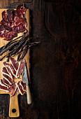 Entenschinken, Bresaola und Beef Jerky auf Holzschneidebrett