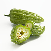 A whole and a halved bitter cucumber on a white background