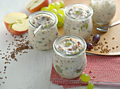 Autumnal fresh grain muesli with apples and grapes in a glass