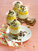 Small cheesecakes in a glass with mango cubes and cream