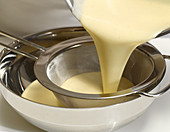 Passing vanilla cream through a sieve